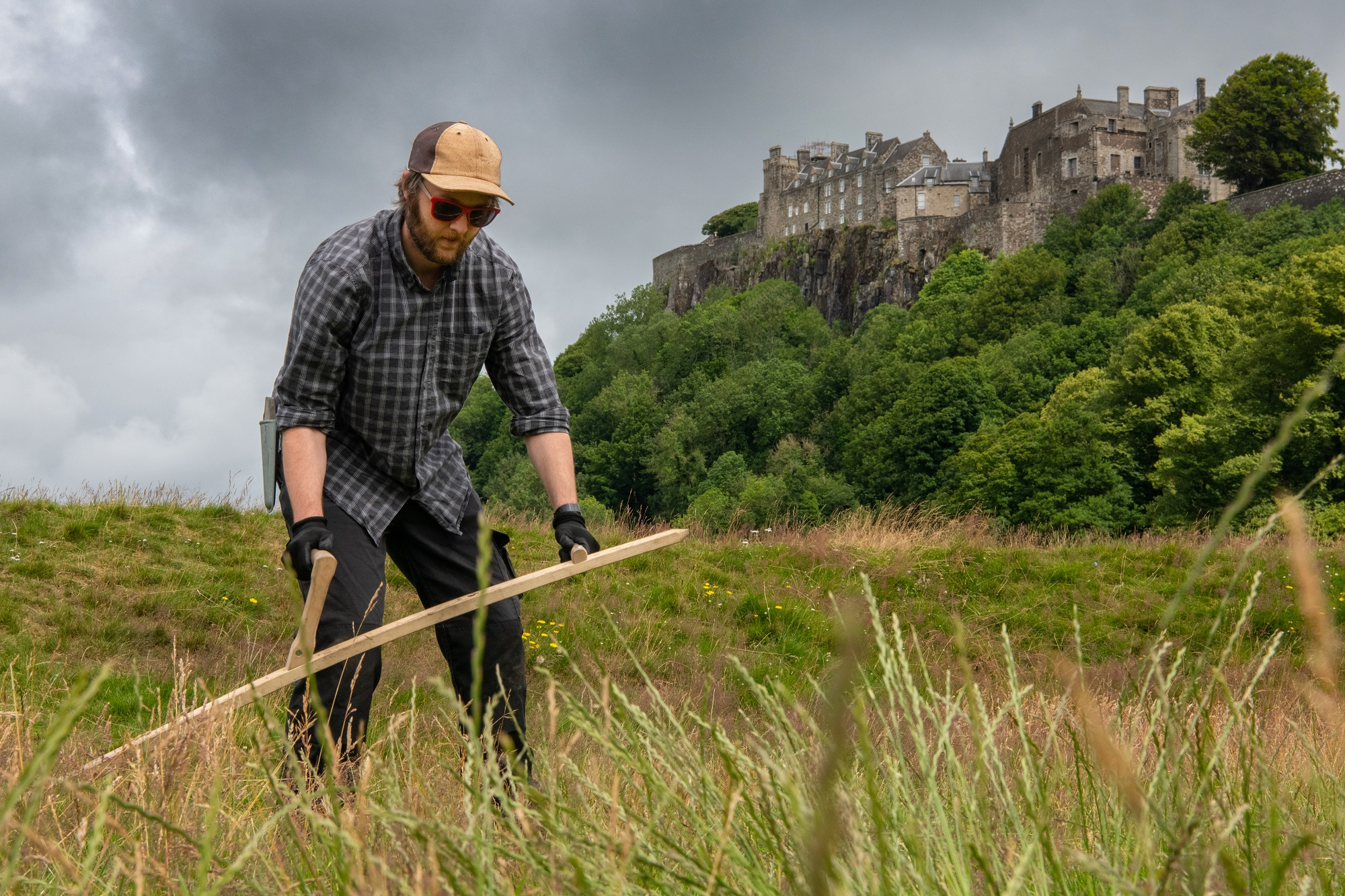 A man cutting grass with a scythe with a castle in the background
